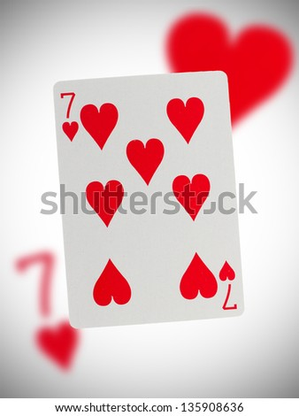 Playing card with a blurry background, seven of hearts