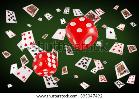Playing cards an dice flying at the poker table. - stock photo