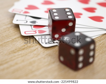 Playing cards and dice on wooden table close-up