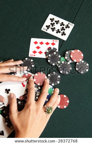 Playing cards, chips and player pulling winnings to herself on a green felt poker table