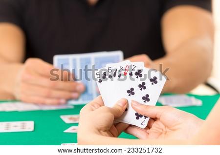 Playing cards closeup of hands holding deck cuarenta traditional Ecuadorian game - stock photo