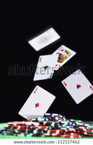 Playing cards falling on pile of gambling chips - stock photo
