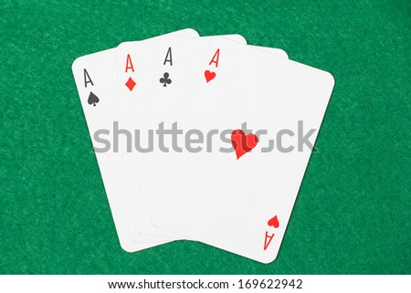 playing cards - four aces on green table - stock photo
