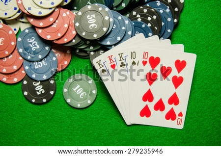 Playing cards 'Full House' and chips on green background - stock photo