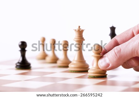 Playing chess - a hand moving white pawn on a chessboard - stock photo