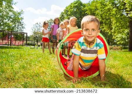 Playing crawling though tube on the lawn - stock photo