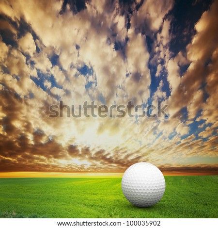 Playing golf. Ball on green golf field at sunset - stock photo