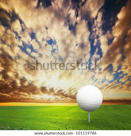 Playing golf. Ball on tee, green golf field at sunset - stock photo