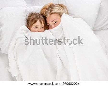 playing joyful mother and her little daughter in the bed, shot from above - stock photo