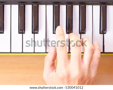Playing mini digital piano, F, on wooden table
