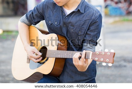 Playing on acoustic guitar outdoor - stock photo