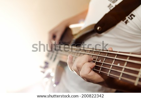 Playing on electric Bass guitar - stock photo