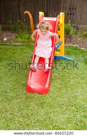 Playing on plastic slide in a backyard - stock photo