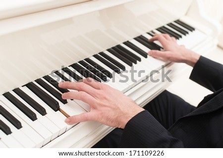 Playing piano. Close-up top view of man playing piano  - stock photo