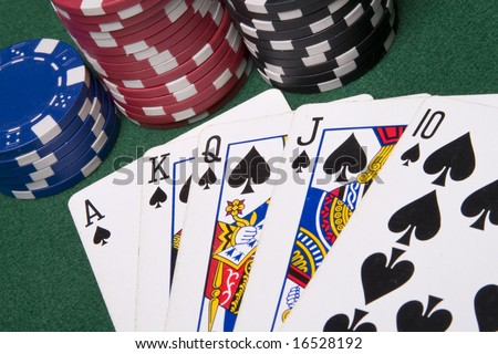 Playing poker cards and several casino chips spread on a green poker table - stock photo