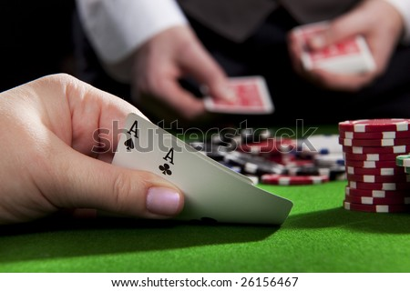 Playing poker in the casino with winning hand (ace pair) - stock photo