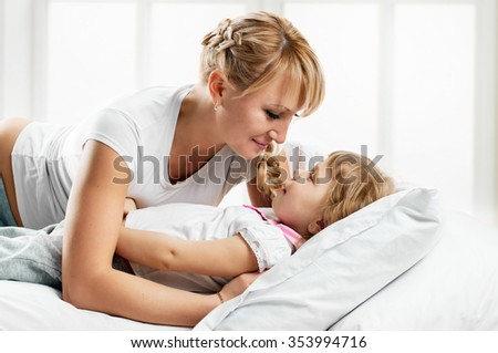 playing Young mother and her daughter in white bed on light window background - stock photo