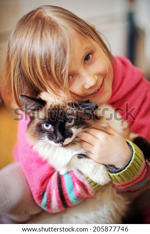 Plays a girl and with a cat in nature - stock photo