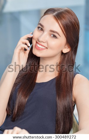 Pleasant conversation. Nice young business woman holding mobile phone and talking on it while expressing joy. - stock photo