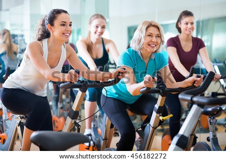Pleasant elderly and young women working out hard in sport club