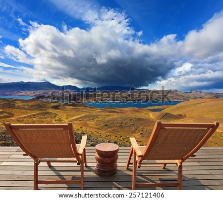 Pleasant holiday. Chile. Wooden chairs in the park Torres del Paine. On the horizon is visible snow-covered  mountain - stock photo