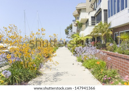 Pleasant path along the waterfront,Naples,Southern California.Flowers line paved walkway,quiet neighborhood near water.Tall masts of sailboats in background.Row of expensive townhomes.Clear blue sky. - stock photo