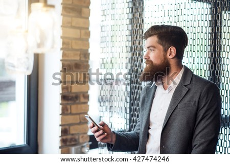 Pleasant positive  bearded man holding cell phone
