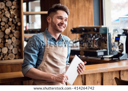 Pleasant waiter  holding tablet