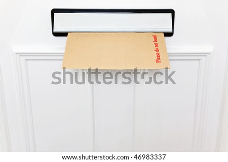 Please do not bend envelope in a letterbox of a white front door, space to add your own text. - stock photo