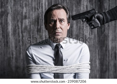 Please no! Tied up businessman caught by a criminal aiming his head with gun  - stock photo