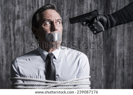 Please no. Tied up businessman with adhesive tape on his mouth sitting in front of the dirty wall while someone aiming his head  - stock photo