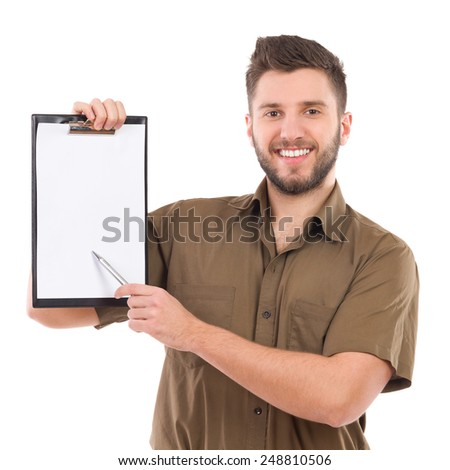 Please sign here. Happy courier holding a clipboard in one hand and pointing with a pen. Waist up studio shot isolated on white. - stock photo