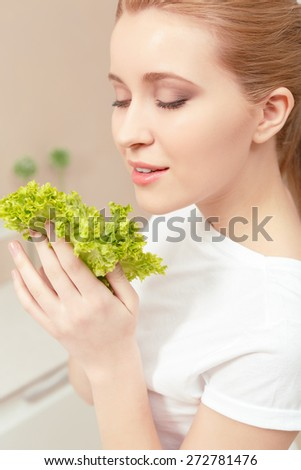 Pleased and smiling. Young woman in the kitchen smiling with her eyes closed and holding lettuce leaves near her face enjoying the freshness of them - stock photo