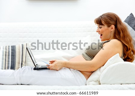 Pleased beautiful pregnant woman sitting on sofa with laptop and credit card - stock photo