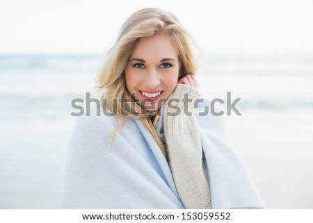 Pleased blonde woman covering herself in a blanket on the beach - stock photo