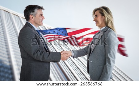 Pleased businessman shaking the hand of content businesswoman against american flag and skyscraper - stock photo