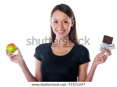 pleased  girl with chocolate and apple in the hands on a white background - stock photo