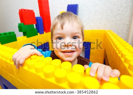 Pleased kid boy playing toy blocks - stock photo
