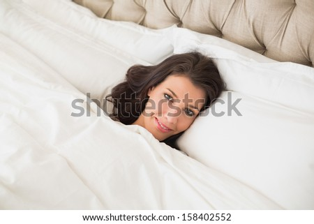 Pleased pretty brown haired woman relaxing in her bed in a bright bedroom