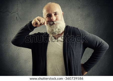 pleased senior man twirling his mustache and looking at camera over dark background