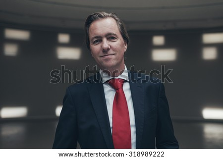 Pleased young businessman wearing suit with red tie in empty room.