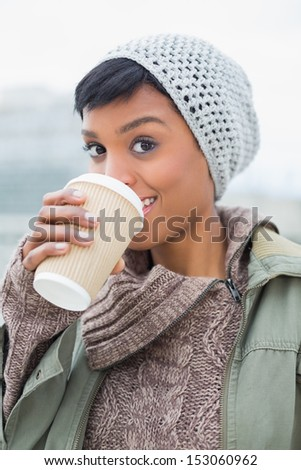 Pleased young model in winter clothes enjoying coffee outside on a cloudy day - stock photo