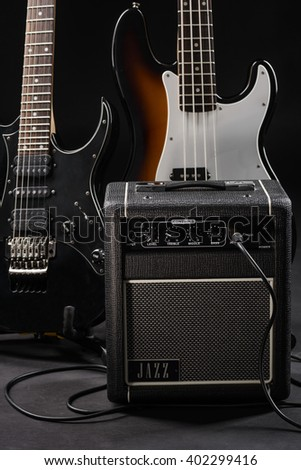 Pleasure for musician's eye to see the composition made of two guitars (electric and bass) and connected guitar amp. Photo shoot in a studio. - stock photo