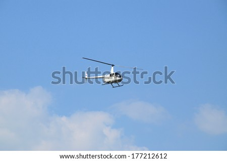 Pleasure lightweight helicopter in flight at low altitude, against the blue sky, front-side view. Flying on a pleasure helicopter - a popular pastime at the weekend