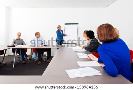 Plenary meeting of a small company, gathered in a meeting room around a flip over - stock photo