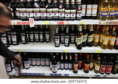 PLENEUF VAL ANDRE, FRANCE - JULY 21: A person takes a bottle from aisle filled with spirits in a E.Leclerc hypermarket on July 21, 2014 in pleneuf-val-andre, France  - stock photo