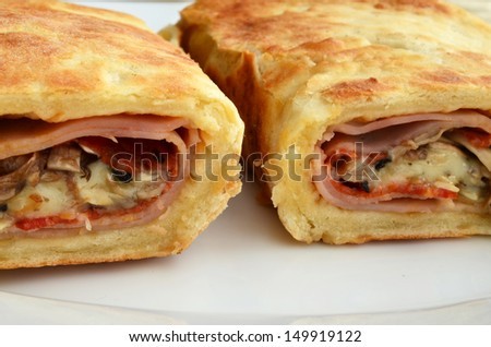 Plentiful, copious ham, cheese, sausage and mushroom sandwich with spices, wrapped in homemade bun, served in white, porcelain plate on golden tablecloth, extreme close up - stock photo