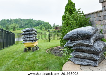 Plenty Bagged Mulches on Top of the Table and Garden Wagon, Preparation for Backyard Mulching - stock photo