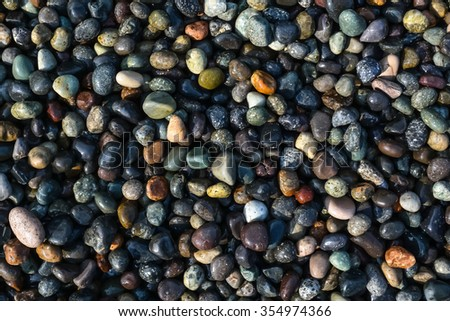 Plenty of colorful pebbles on the seashore. - stock photo