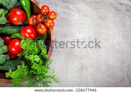 Plenty of colorful vegetables in wooden plate on linen background;  - stock photo